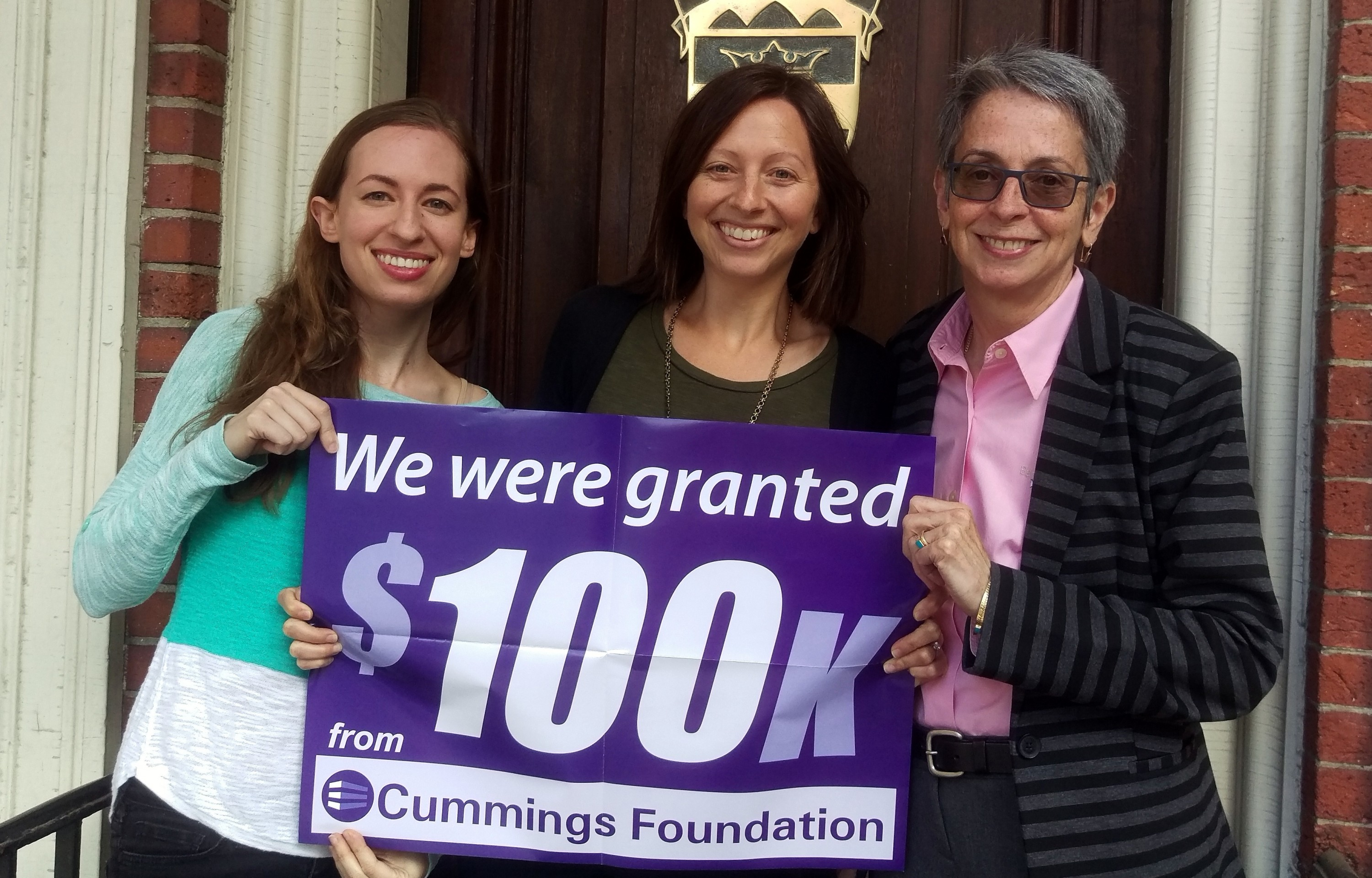 Clearinghouse staff hold the poster announcing their grant from Cummings Foundation. L to R: Communications Coordinator Hilary Vaught, Access to Justice Fellows Program Director Mia Friedman, and Executive Director Maribeth Perry.